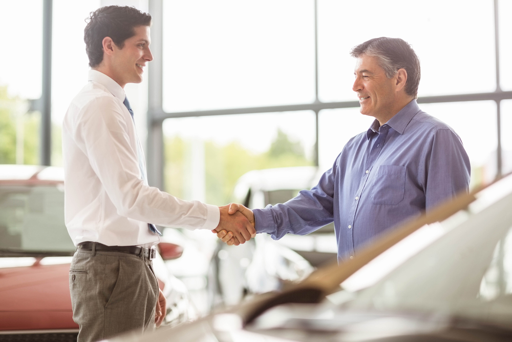 Businessman shaking a customer hand at new car showroom-1